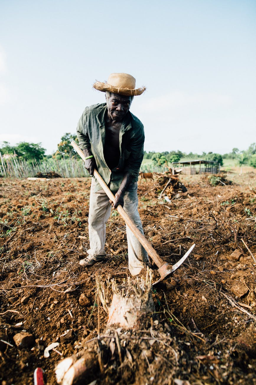 photo of man standing while holding pickaxe